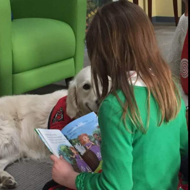 Lucy the dog with girl reading a book to her